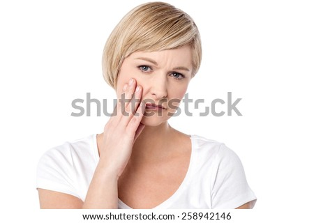 Upset middle aged woman her hands on cheek - stock photo