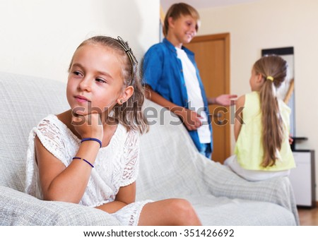 Upset morose girl is jealous sister of stepbrother indoors - stock photo