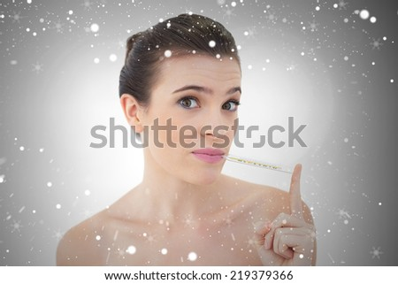 Upset natural brown haired model using a thermometer against snow - stock photo