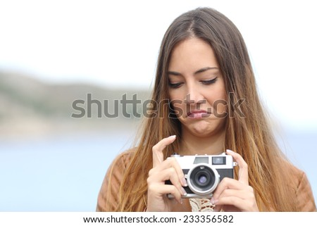 Upset photographer woman looking her old slr photo camera disgusted with the sea in the background - stock photo