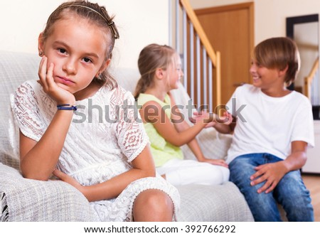 Upset sad little girl is jealous sister of stepbrother indoors - stock photo