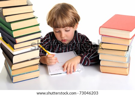 Upset schoolboy doing homework between stacks of books. isolated on white. - stock photo