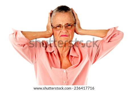Upset senior covering her ears . - stock photo