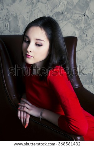 upset teenage girl sitting in the chair - stock photo