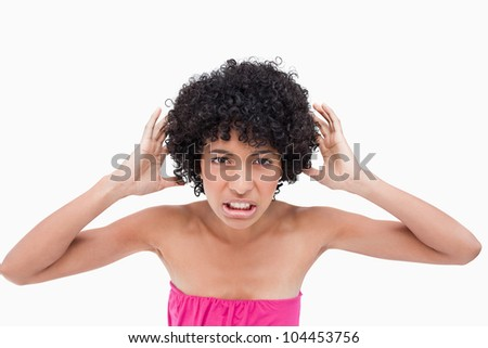 Upset teenage placing her hands beside her ears because of the noise - stock photo