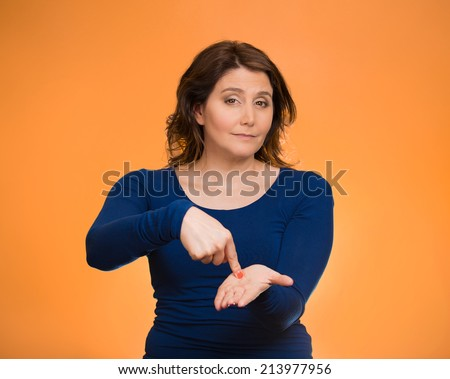 Upset woman gesturing pay me my money back, finger on palm gesture, isolated orange background. Human face expression, emotions, feeling body language, non verbal communication. Financial debt concept - stock photo