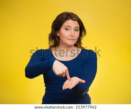 Upset woman gesturing pay me my money back, finger on palm gesture, isolated yellow background. Human face expression, emotions, feeling, body language non verbal communication. Financial debt concept - stock photo