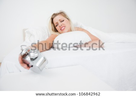 Upset woman looking at her alarm clock while lying in her bed - stock photo