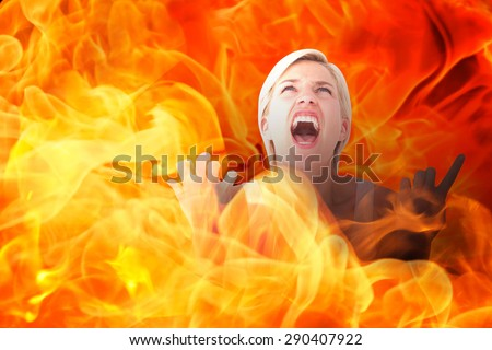 Upset woman screaming with hands up against fire - stock photo