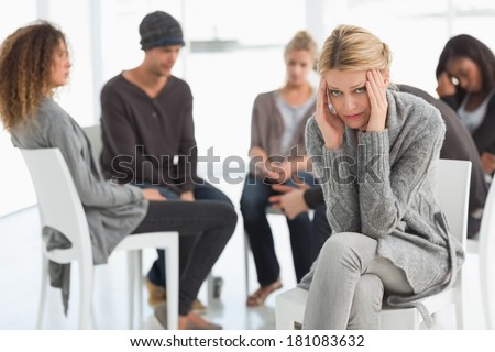 Upset woman with head in hands at rehab group looking at camera at therapy session - stock photo
