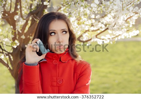 Upset  Woman with Inhaler  in Spring Blooming Decor - Portrait of a woman having respiratory problems from allergies surrounded by seasonal flowers   - stock photo