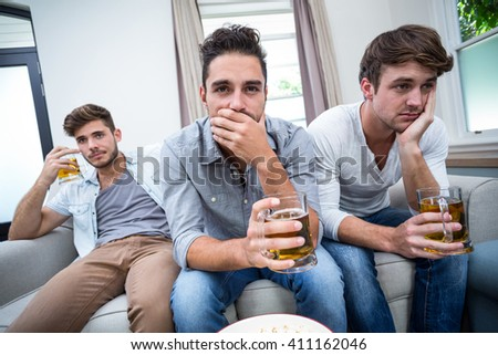 Upset young male friends drinking alcohol while watching TV at home - stock photo