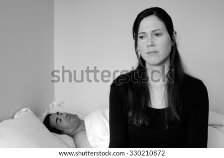 Upset young woman in her thirties (30s)having problems with sex. Focus on the woman in the foreground and the man in bed in the background. Sex and relationship concept (BW) - stock photo