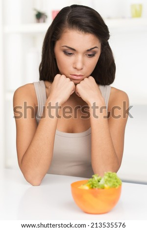 upset young woman keeping diet and eating vegetables. Sad woman in front of her small diet meal - stock photo