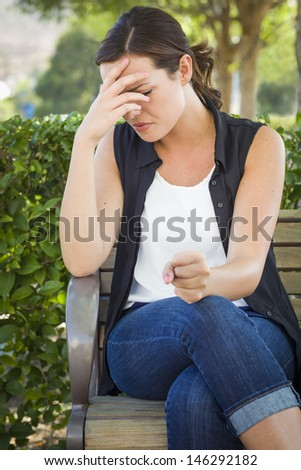Upset Young Woman Sitting Alone on Bench Outside with Her Head in Her Hand and Clinched Fist. - stock photo
