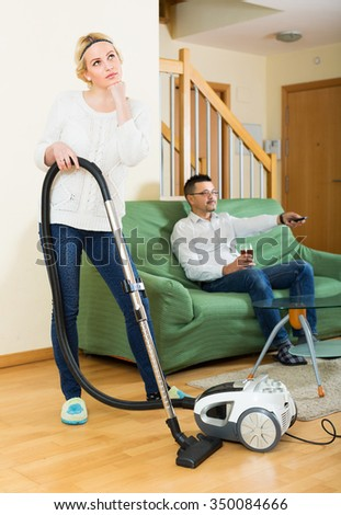Upset young woman with hoover looking at man on sofa watching TV