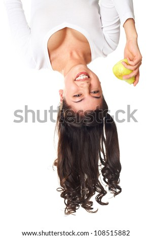 Upside down image of a lovely young woman holding a pear - stock photo