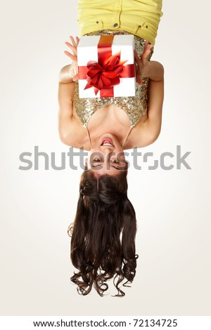 Upside down view of young girl with giftbox on white background - stock photo