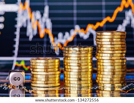 Uptrend stacks coins, dices cube with the word GO on the financial stock charts as background. Selective focus - stock photo