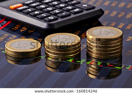 Uptrend stacks of euro coins, calculator and financial chart as background. Selective focus - stock photo