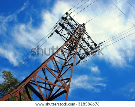 Upward view diagonally to the power line and pylon against a blue sky with clouds - stock photo