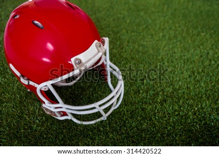 Upward view of an american football helmet on the field