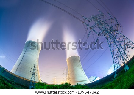 upward view of the cooling towers and high voltage power transmission tower at night - stock photo