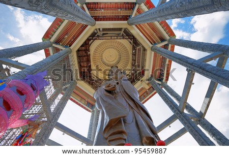 Upward view of the iconic bronze statue of the buddhist goddess of mercy known as Kuan Yin in Kek Lok Si buddhist temple in Air Itam, Penang, Malaysia against a blue cloudy sky. This is a HDR image. - stock photo