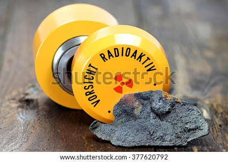 uraninite with storage container for radioactive materials (translation: caution - radioactive) - stock photo
