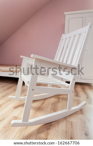 Urban apartment - white rocking chair in girl's room - stock photo