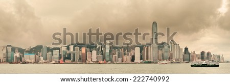 Urban architecture in Hong Kong Victoria Harbor with city skyline and cloud in the day with yellow tone.