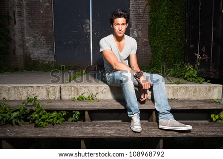 Urban asian man sitting on stairs. Good looking. Cool guy. Wearing grey shirt and jeans. Old neglected building in the background.