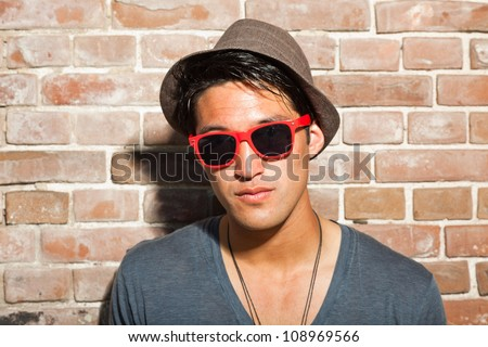 Urban asian man with red sunglasses. Good looking. Cool guy. Wearing grey shirt and hat. Standing in front of brick wall. - stock photo