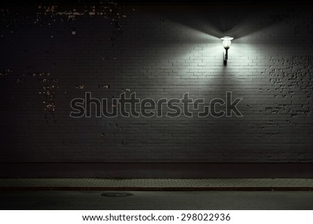 Urban background. Brick wall under the lamp light at night. - stock photo