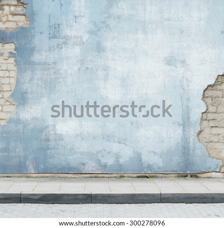 Urban background. Grunge obsolete street wall and pavement.