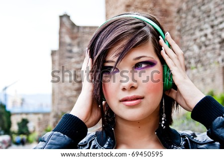 Urban beautiful girl, concentrated in music - stock photo