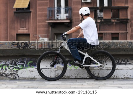 Urban bike rider with old fashioned building in background. - stock photo