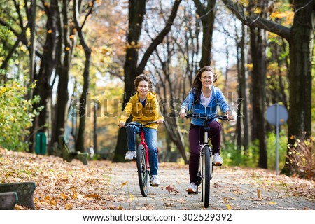 Urban biking - girl and boy riding bikes in city park