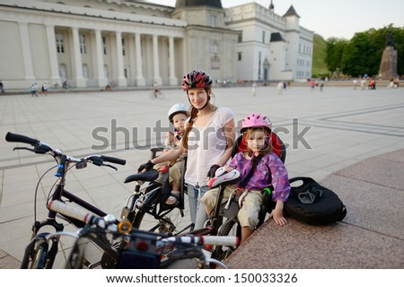 Urban biking - young mother with kids in a city - stock photo