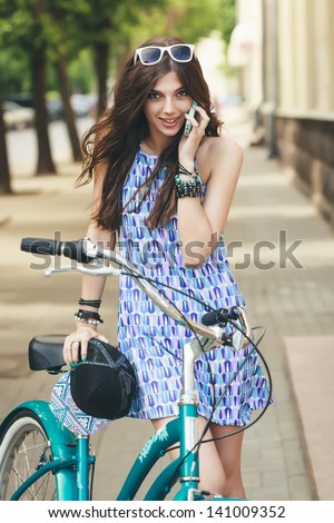 Urban biking. Young woman with bike is talking by phone. Active people. Outdoors, lifestyle - stock photo