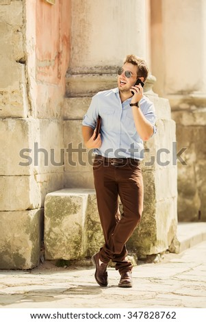 Urban business man talking on smart phone at walking - stock photo