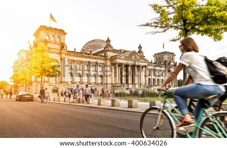 Urban city life with famous Reichstag building in the background in beautiful golden evening light at sunset in summer with retro vintage Instagram style pastel toned filter effect, Berlin, Germany - stock photo