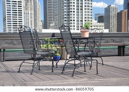 Urban City Rooftop Deck Furniture High Rise Buildings in the Background - stock photo