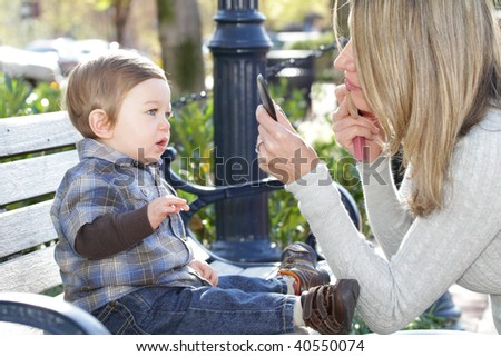 Urban, city scene: young mother putting on make on, her son, baby boy, sitting on a bench - stock photo