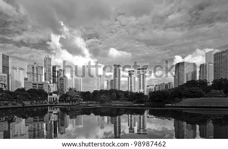 Urban city skyline of Kuala Lumpur city centre with reflection of skyscrapers in the lake in monochrome. Kuala Lumpur is the capital of Malaysia. - stock photo