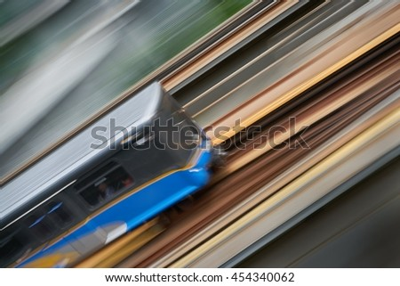 Urban Commuter Rail. An elevated commuter rail car speeds along a track. Motion blur.                                  - stock photo