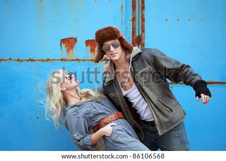 Urban couple swinging pose on grunge background - stock photo