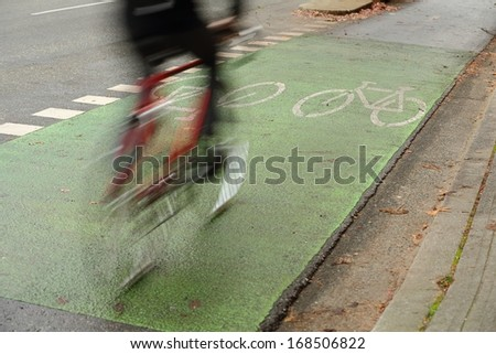 Urban Cycle Path, Vancouver. A cyclist using the designated bicycle lane which is separated from vehicle traffic in downtown Vancouver, British Columbia, Canada. - stock photo