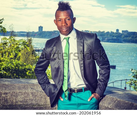 Urban Fashion. Dressing in a black blazer, green necktie, white undershirt,  green pants, hands in pocks, a young black guy with mohawk hair is standing by river, looking at you. Modern Business Man. - stock photo