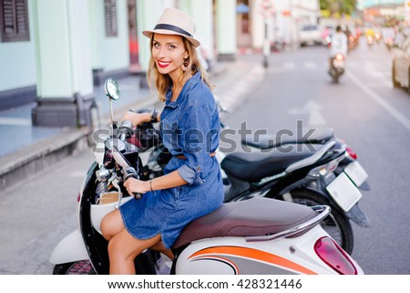 Urban fashion. Outdoor portrait of pretty young woman with red lips make-up in hat sitting on scooter.